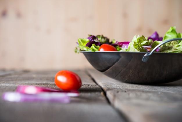 close-up-de-ensalada-de-verduras-frescas-en-el-recipiente-con-fondo-de-madera-rustica-de-edad-concepto-de-alimentos-saludables_1150-1838