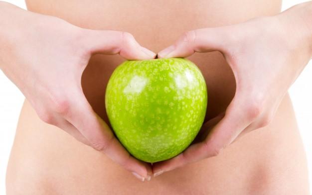 detalle-de-manos-de-mujer-sosteniendo-una-manzana-verde_1301-3455